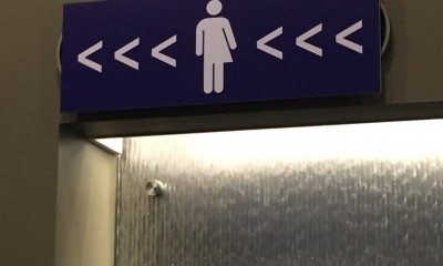 Gender-neutral bathroom sign, translation services