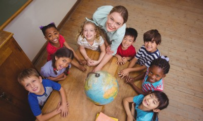 46212807 - cute pupils smiling around a globe in classroom with teacher at the elementary school