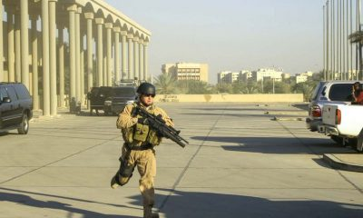 19108179 - a heavily-armed operator from blackwater usa sprints into position as an incoming helicopter approaches an exfiltration site for a diplomatic meting in baghdad, circa december 2006