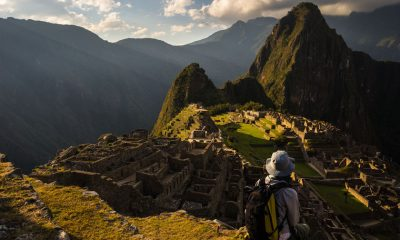 45568731 - machu picchu illuminated by the last sunlight. the inca's city is the most visited travel destination in peru. one person sitting in contemplation.