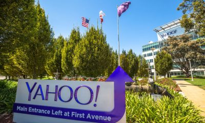 63408830 - sunnyvale, california, united states - august 15, 2016: flags in front of yahoo headquarters main entrance in sunnyvale with american flag and flag with yahoo icon.