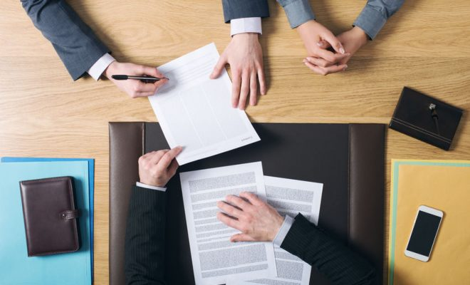 39447143 - business man and woman sitting at the lawyers's desk and signing important documents hands top view unrecognizable people