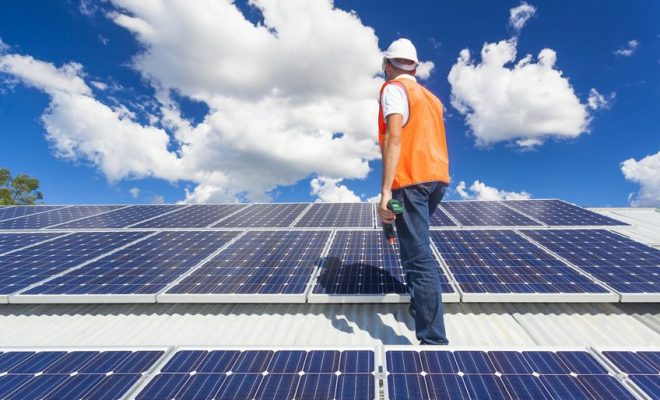 21361836 - young technician checking solar panels on factory roof